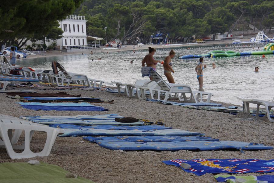 Makarska, 120815. U gradu koji zivi od turizma, a glavni proizvod sto se turistima nudi su sunce i more, mjesto na plazi u jeku sezone je dragocijeno. Tako mnogi turisti ustaju rano i zauzimaju mjesto na zalu prostrtim rucnicima. Situaciju dodatno kompliciraju neki iznajmljivaci lezaljki koji, suprotno gradskim propisima, prekriju svoj dio plaze lezaljkama. Na fotografiji : Makarska glavna plaza u 7 sati ujutro. Foto: Ivo Ravlic / CROPIX